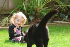L'enfant en bas âge heureux rit comme promenades de chat vers elle Photographie stock