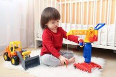 L'enfant en bas âge joue des voitures Photos stock