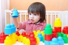 L'enfant en bas âge joue les blocs en plastique à la maison Images stock