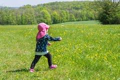 L'enfant en bas âge joue sur le pré estival de fleur avec des bulles de savon photographie stock libre de droits