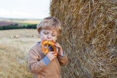 L'enfant en bas âge mignon mangeant le bretzel allemand goden dessus le gisement de foin Image libre de droits