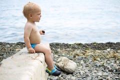 L'enfant en bas âge mignon s'assied sur le parapet en pierre sur le bord de la mer Copiez l'espace Image stock