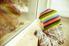 L'enfant en bas âge regarde à la fenêtre Photos libres de droits