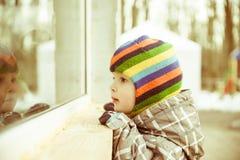 L'enfant en bas âge regarde à la fenêtre photographie stock libre de droits