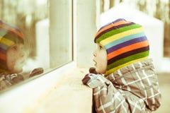 L'enfant en bas âge regarde à la fenêtre Photos stock