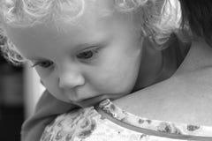 L'enfant en bas âge regarde au-dessus de l'épaule de sa grand-mère Image stock