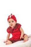 L'enfant en bas âge s'est habillé dans des vêtements rouges se reposant sur la couverture sur le fond blanc Photo stock