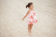 L'enfant en bas âge sautant sur le sable Photos libres de droits