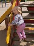 L'enfant en bas âge heureux criant sur la glissière en bois fait un pas Image libre de droits