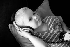 L'enfant entend la musique avec des écouteurs photo libre de droits