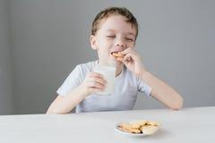 L'enfant est heureux de manger les biscuits faits maison avec du lait Photos stock