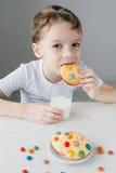L'enfant est heureux de manger les biscuits faits maison avec du lait photos libres de droits