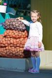 L'enfant est les sacs proches debout avec des pommes de terre photos libres de droits