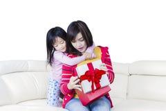 L'enfant et la mère ouvrent une boîte de présents Images stock