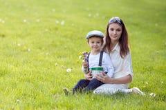 L'enfant et la maman de Beautful au printemps se garent, fleurissent et se présentent mères Photographie stock