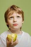 L'enfant et la pomme de sept ans Image stock