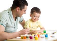 L'enfant et le papa peignent ensemble d'isolement sur le blanc photos libres de droits