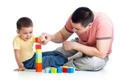 L'enfant et son papa jouent avec les blocs constitutifs image stock