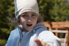 L'enfant examine avec indignation le cadre et les points un doigt en avant L'opinion exprime le mécontentement Peu fille blanche images stock