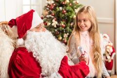 L'enfant féminin mignon souhaitant des sorts se présente la nuit Noël images stock