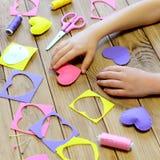 L'enfant a fabriqué des coeurs à partir de le feutre Mains du ` s d'enfants sur la table Cadeaux faits main de coeur de jour de v Images libres de droits