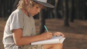 L'enfant fait des croquis dans le carnet sur le fond en bois banque de vidéos