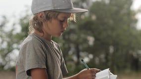 L'enfant fait des croquis dans le carnet sur le fond en bois clips vidéos