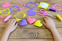 L'enfant a fait des ornements d'un coeur de feutre L'enfant montre les métiers simples d'un feutre pour le jour du ` s de Valenti Image libre de droits