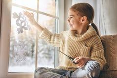 L'enfant fait les flocons de neige de papier photo libre de droits