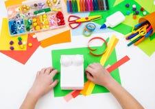 L'enfant fait un caméléon de boîte d'entaille Matériel pour la créativité sur un fond blanc images libres de droits