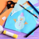 L'enfant a fait une carte de papier avec un bonhomme de neige, flocons de neige et les mots I aiment l'hiver Ciseaux, bâton de co Images stock