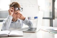 L'enfant fatigué travaille dans le bureau Images libres de droits