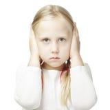L'enfant a fermé ses mains au-dessus de ses oreilles Photographie stock libre de droits