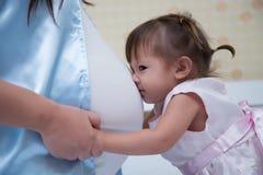 L'enfant gai et heureux de famille embrassant la mère enceinte montre l'amour Photo stock