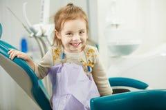 L'enfant gai s'assied dans la chaise de dentiste avec la serviette sur le coffre photographie stock libre de droits