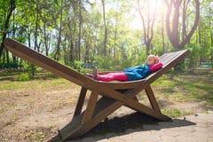 L'enfant gai se trouve sur le banc en bois dans un jour ensoleillé Image stock