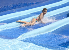 L'enfant glisse un waterslide Photographie stock