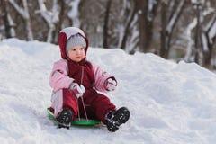 L'enfant glisse vers le bas une colline sur un traîneau photos libres de droits