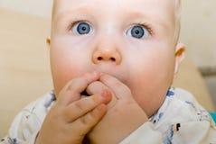 L'enfant goûte un jouet photo stock