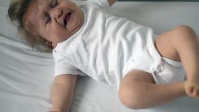 L'enfant handicapé d'un an dans la combinaison blanche essaye de rouler sur le lit banque de vidéos