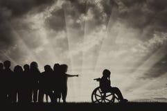 L'enfant handicapé dans pleurer d'un fauteuil roulant et les enfants l'ont chassé photo libre de droits