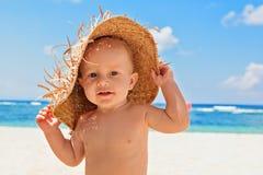 L'enfant heureux avec la paille a eu sur la plage des vacances de famille images libres de droits