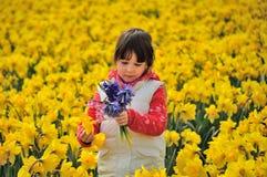 L'enfant heureux avec le ressort fleurit sur les jonquilles jaunes mettent en place, petite fille des vacances aux Pays-Bas Images libres de droits