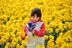 L'enfant heureux avec le ressort fleurit sur les jonquilles jaunes mettent en place, petite fille des vacances aux Pays-Bas Photo stock