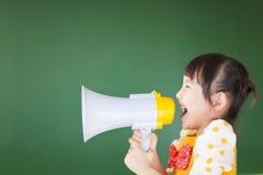 L'enfant heureux crie quelque chose dans le mégaphone Image stock