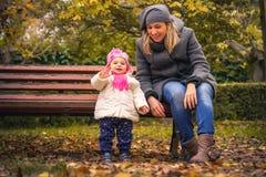 L'enfant heureux de bébé disent bonjour la mère d'automne de parc Photos stock