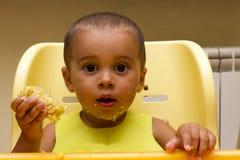 L'enfant heureux gai de bébé se mange avec une cuillère Photographie stock