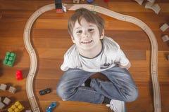 L'enfant heureux jouant avec des jouets s'exercent et railroad tout en se reposant sur le plancher en bois dans sa chambre Vue su Photo libre de droits