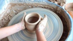 L'enfant heureux presse Clay Vase sur la roue, enfant travaille à la roue de poterie lentement et moule un vase, petit blond banque de vidéos