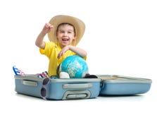 L'enfant heureux s'asseyant dans la valise s'est préparé aux vacances Image libre de droits